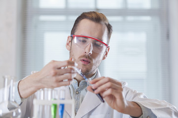 young scientist fills the vial with a syringe