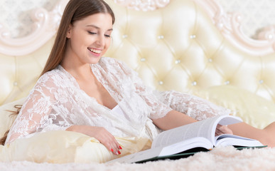 Beautiful young girl reading a book in bed