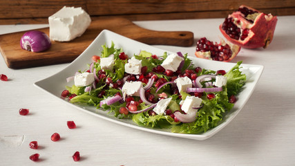 Fresh healthy green salad with pomegranate seeds, onion and feta cheese