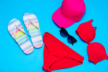 beautiful swimsuit, sunglasses, cap and sandals on the wonderful blue background