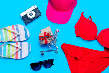 beautiful swimsuit, sunglasses, camera, gifts in shopping cart, cap and sandals on the wonderful blue background