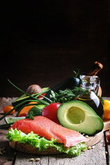 Selection of healthy and wholesome foods: fish, vegetables and herbs, old wooden background, selective focus