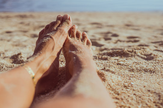 woman legs on sand beach