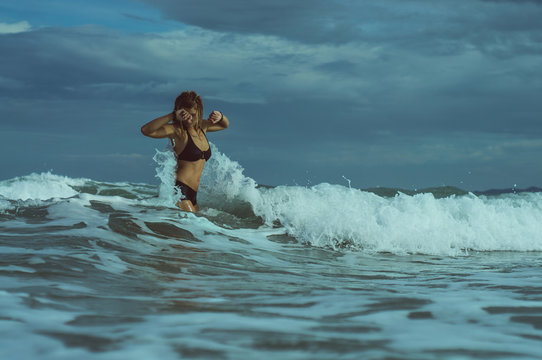 girl jumping in the waves of the sea. vinage color style