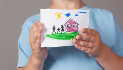 Child holds a drawn house with family in his hands