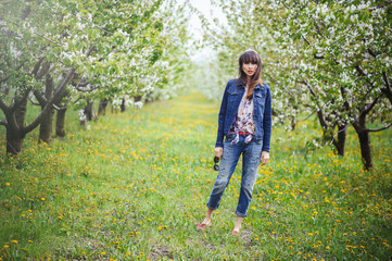 woman in jeans in cherry orchard
