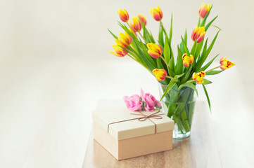Beautiful bouquet of tulips in glass vase on table, ready to make a present with gift box for beloved person