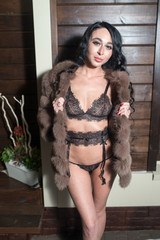 Beautiful sexy young woman in fur coat and underclothes