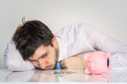 Young worried man has empty piggy money bank.
