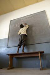 Madagascar, Fianarantsoa, Schoolboy writing on blackboard