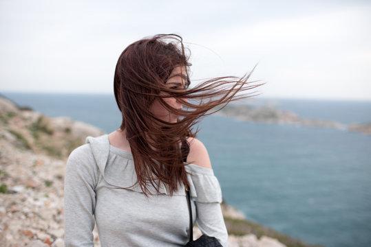 Fille cheveux au vent bord de mer