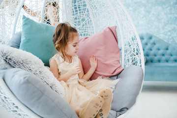 Little girl in fancy beige dress sits in large chair with many pillows