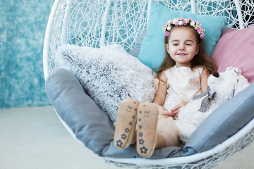 Little girl looks at her feet sitting in white hanging chair