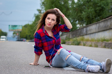 Beautiful young girl sitting on road