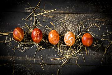 bunte Ostereier mit Zwiebelschalen gefärbt auf schwrzen Holztisch