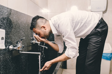 Muslim washing his nose and mouth before the obligatory prayer