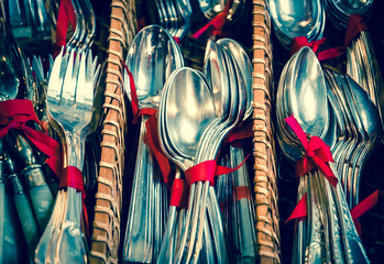 Old silver cutlery tied together with red ribbon in wicker basket. Flea market in Paris (France)