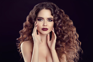 Beauty girl portrait. Beautiful young woman with long curly hair, makeup and manicured nails isolated on black background.