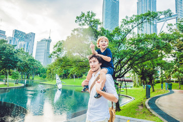 Father and son travelers in Malaysia against a background towers Patronas twins. Traveling with children concept
