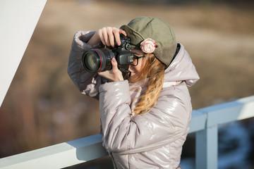 Young european woman photographer enjoying first spring sun exploring suburban locations railway bridge