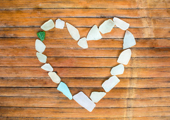 Heart from sea glass on wooden background. Sea glass mosaic for St. Valentines Day.