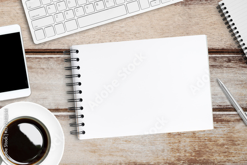 Blank notebook on top of wood office table Top view flat lay