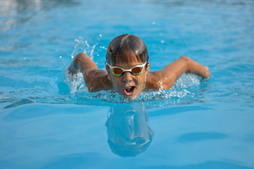 Close up action swimming boy butterfly style with gogles
