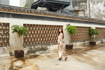 Young woman in long dress by decorative building with plants