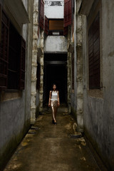 Young woman walking down narrow alley between buildings