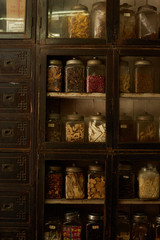 Glass jars on shelves with traditional Chinese herbal medicine
