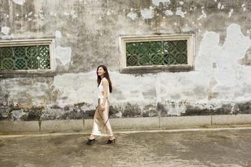 Woman in long dress walking past building