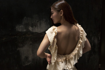 Young woman wearing frilly dress, rear view