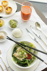 Vegetable and noodle dish on table with chopsticks