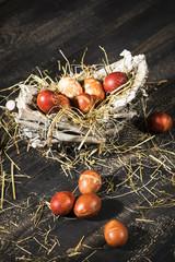 Ostereier (mit Zwiebelschalen gefärbt)  in einem Körbchen auf schwarzen Holztisch