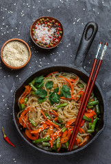 Spicy rice (potato) noodles with vegetables - carrots, bell peppers, green beans, ginger, and sesame seeds. Traditional popular dish of Asian cuisine. Cellophane, glass noodle. Selective focus