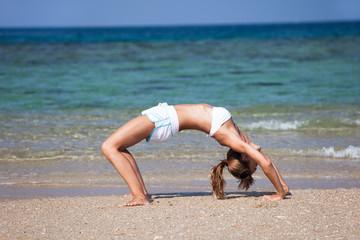 femme en été qui fait le pont sur une belle plage