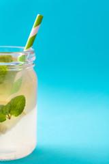 Lemonade drink in a jar glass on blue background. Copyspace.