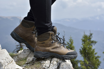 hiking boots on the rock in the mountains. woman hiker stand on mountain peak rock