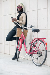 Smiling woman with phone near bike