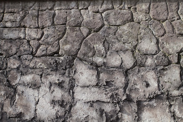 Background image of an old stone wall with cracks and remains of plaster