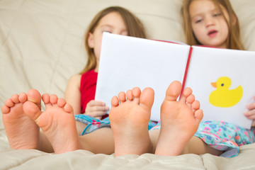 Children reading a book in bed