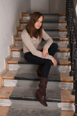 Beautiful brunette girl posing sitting on stairs. Indoors