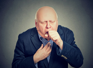 Old man coughing holding fist to mouth