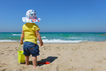 Baby girl toddler with bucket and spade on the beach