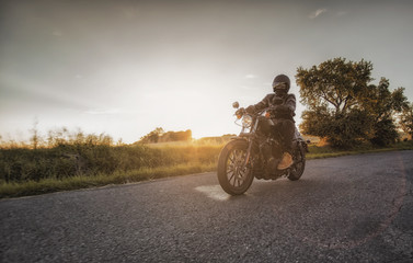 Biker rides his motorcycle along the road during beautiful sunset. Motorbiker's season starts now during spring time.