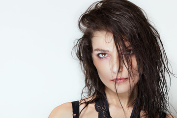 Pretty woman portrait with wet hair and smudged makeup looking