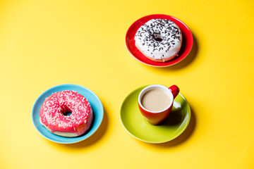 tasty glazed donuts and cup of coffee on plates on the wonderful yellow background