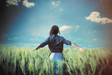 beautiful young woman standing in the middle of the wonderful green field