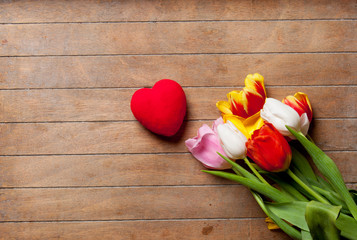 bunch of colorful tulips and heart shaped toy on the wonderful brown wooden background