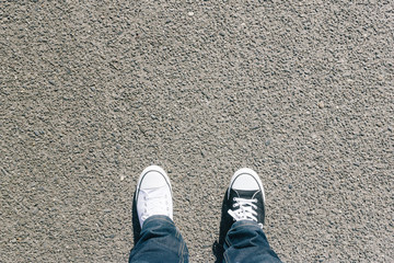 Black and white shoes on asphalt, high angle